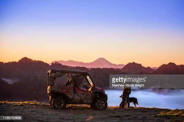 a buggy sits at the top of the mountain to watch the early morning fog as it floods the valley at sunrise. - recreational pursuit stock pictures, royalty-free photos & images