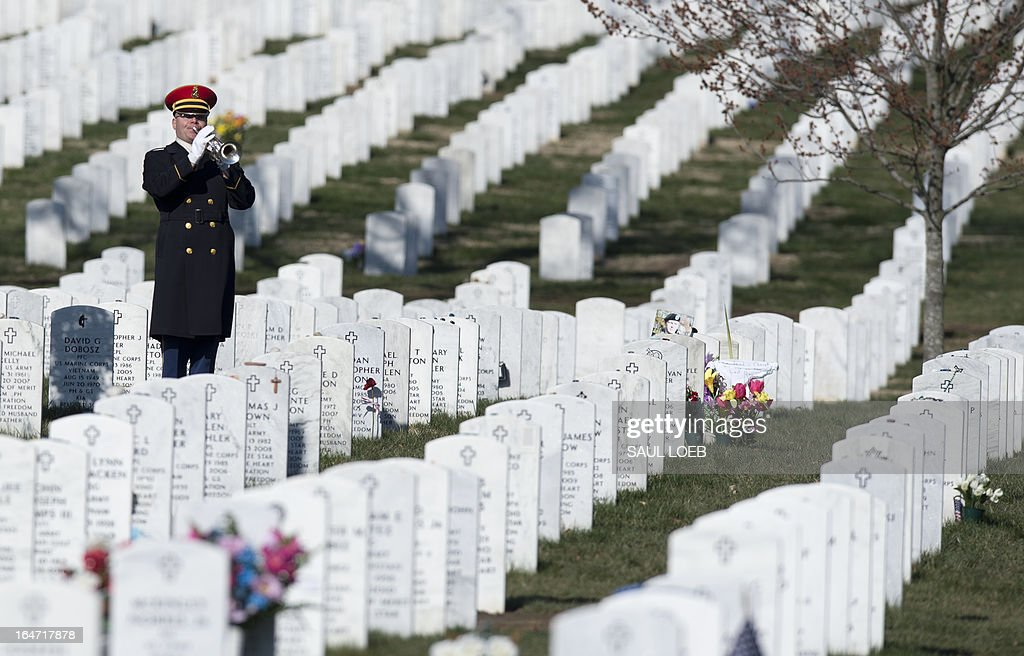 A bugler from the US Army's 3rd Infantry Regiment 'The Old Guard' plays taps during a burial service for US Army Captain Andrew Pedersen-Keel in Section 60 at Arlington National Cemetery in Arlington, Virginia, March 27, 2013. Pedersen-Keel, 28, was killed March 11 during an attack on a police station in Afghanistan. AFP PHOTO / Saul LOEB