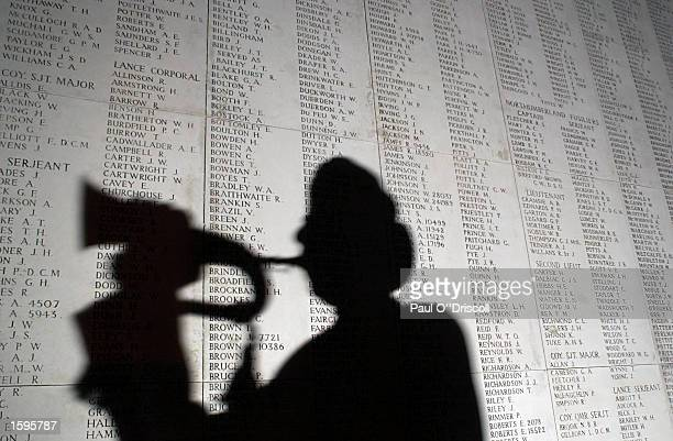 A bugler is silhouetted against part of a list 54896 World War I soldiers who died between 1914 and August 15 1917 and who have no known grave...
