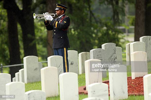 A bugler plays Taps at the funeral of Sgt 1st Class Edward Kramer at Wilmington National Cemetery on July 9 2009 in Wilmington North Carolina Kramer...
