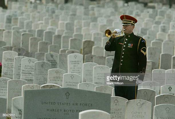 A bugler plays Taps at the funeral of US Army Spc Rodger G Ling at Arlington National Cemetery March 4 2004 in Arlington Virginia Ling was killed...