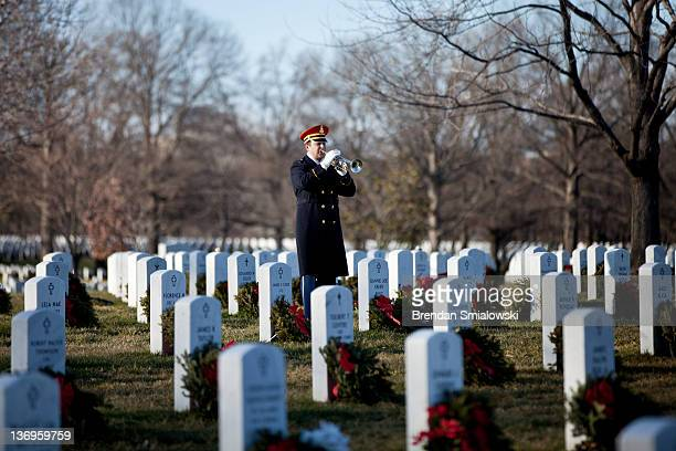 A bugler plays Taps during a burial service at Arlington National Cemetery January 13 2012 in Arlington Virginia US Army Spc Ronald H Wildrick Jr was...