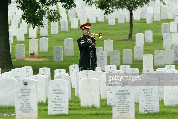 A bugler plays Taps during the funeral of US Army Specialist Brett Christian at the Arlington National Cemetery August 7 2003 in Arlington Virginia...