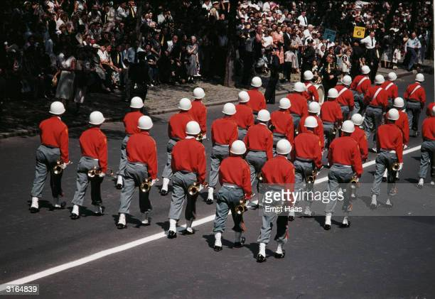 Buglers on parade in New York wearing white steel helmets red sweaters and army gaiters and boots