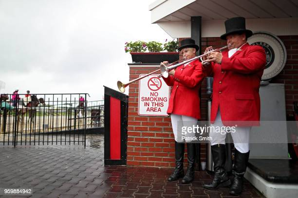 Buglers practice as they attempt to stay dry from the rain prior to the 94th running of the BlackEyed Susan Stakes at Pimlico Race Course on May 18...