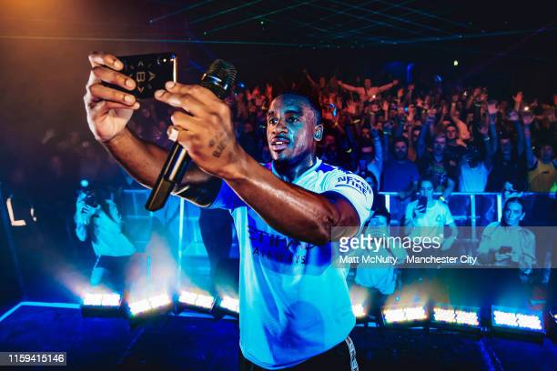 Bugzy Malone takes a selfie on stage during the Manchester City Puma kit launch at Mayfield Depot on June 30, 2019 in Manchester, England.