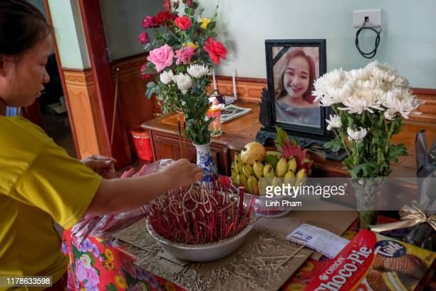 Bui Thi Phuong lights incense at a makeshift shrine with the photo of her younger sister Bui Thi Nhung believed to be one of the 39 victims found...