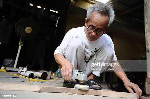 Bui Van Vuoc makes a part of a traditional music instrument at his workshop in Vinh Bao on September 19 2015 in Hai Phong Vietnam 81yearsold Bui Van...