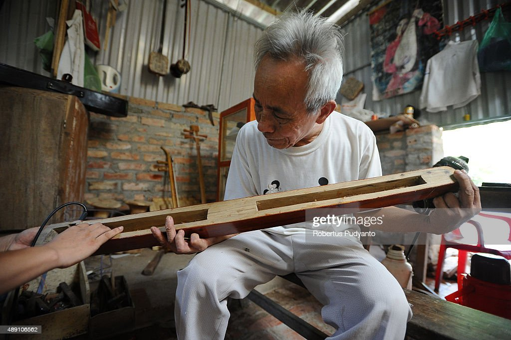 Bui Van Vuoc makes final inspection on dan bau instrument at his workshop in Vinh Bao on September 19 2015 in Hai Phong Vietnam 81yearsold Bui Van...