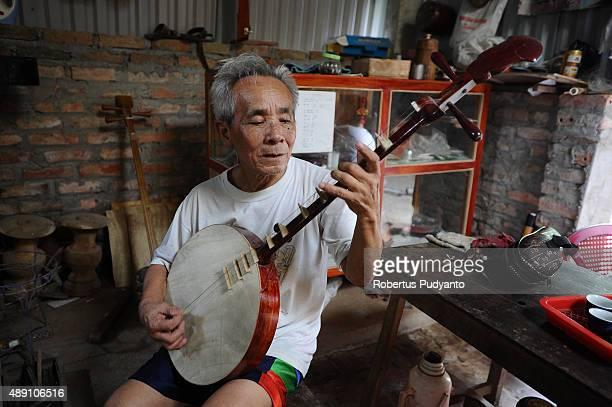 Bui Van Vuoc plays a dan nguyet instrument at his workshop in Vinh Bao on September 19 2015 in Hai Phong Vietnam 81yearsold Bui Van Vuoc of Bao Ha...