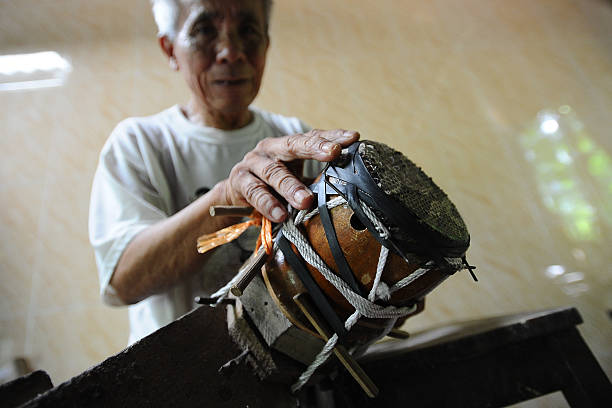 Bui Van Vuoc prepares a part of a traditional music instrument at his workshop in Vinh Bao on September 19 2015 in Hai Phong Vietnam 81yearsold Bui...