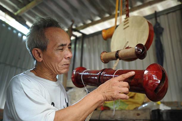 Bui Van Vuoc shows a sao dieu instrument at his workshop in Vinh Bao on September 19 2015 in Hai Phong Vietnam 81yearsold Bui Van Vuoc of Bao Ha Dong...