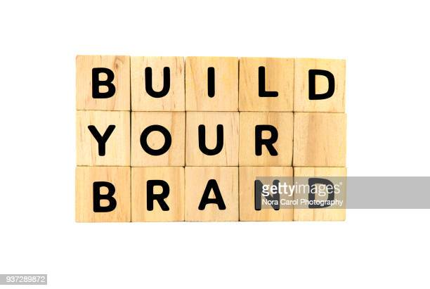 build your brand text on wooden blocks on white background - advertising_campaign stock pictures, royalty-free photos & images