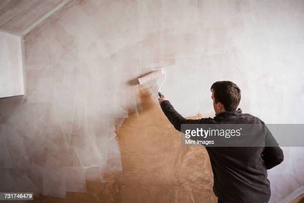 A builder, a painter holding a paint roll, painting a wall with white paint.