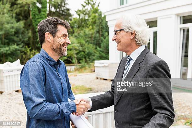 Builder and architect on construction site shaking hands smiling