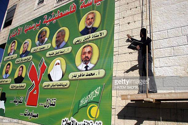 A builder appoints the stone frontage of a newly constructed building adorned with a huge poster of showing the nine Hamas movement candidates that...