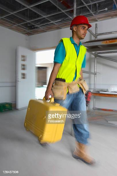 Builder arriving on site with toolbox