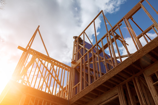 builder at work with wooden roof construction Wood Building frame 911225858