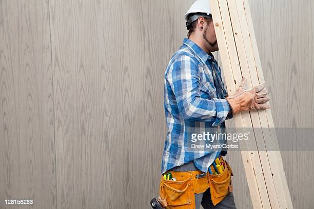 Builder carrying planks