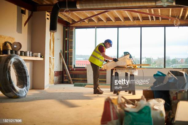 builder checking his plans - headwear stock pictures, royalty-free photos & images