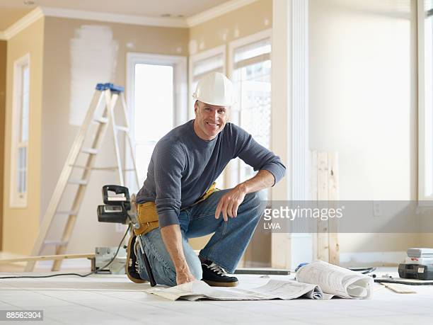 builder consulting floor plans at building site - renovation stock pictures, royalty-free photos & images