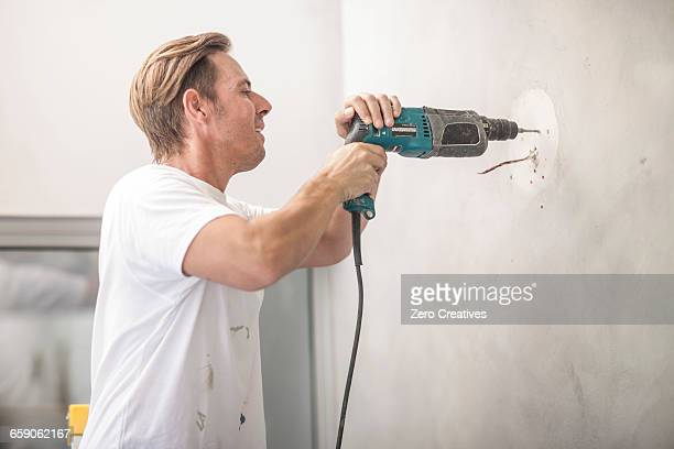 builder drilling into wall - drill stock pictures, royalty-free photos & images
