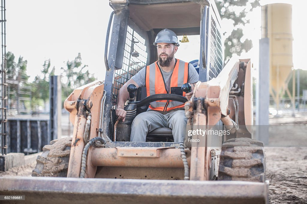 Builder driving excavator on construction site : Stock Photo