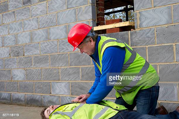 Builder Giving First Aid To An Injured Colleague