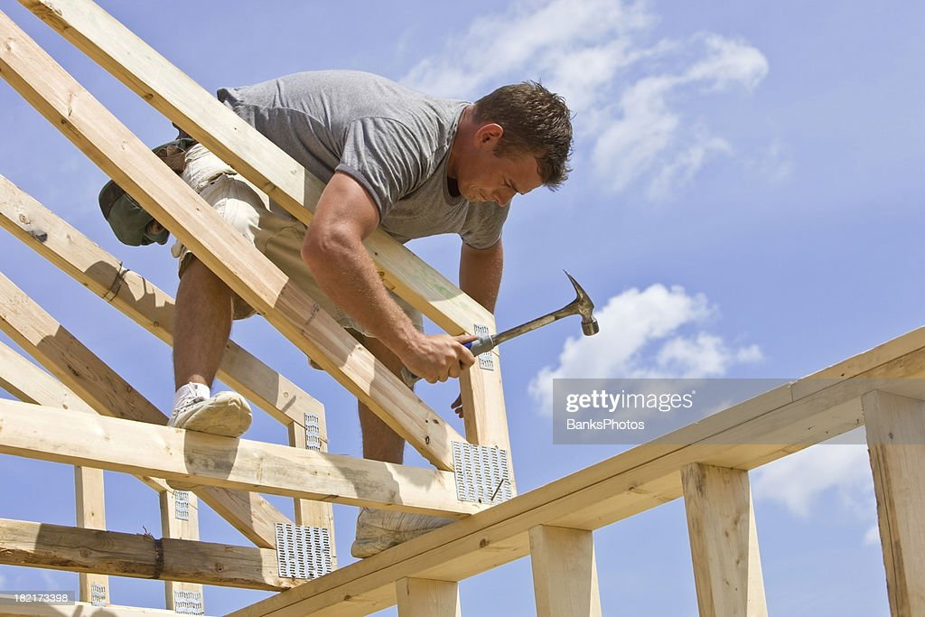 Builder Hammering Roof Truss Nail Against Blue Sky Stock Photo ...