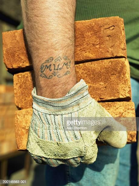 Builder holding bricks, 'Mum' tattooed on wrist, close-up