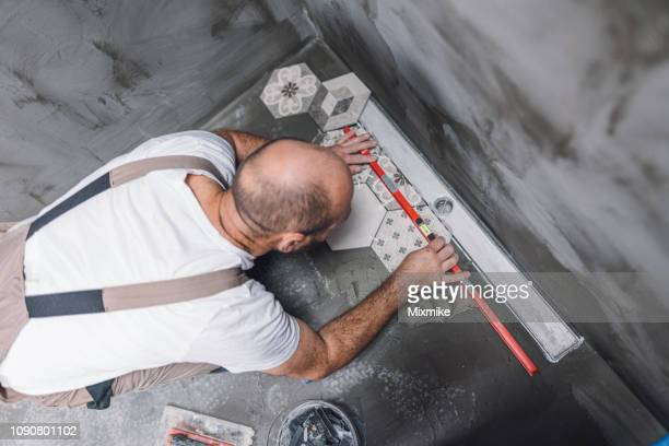 builder leveling the tiles on the bathroom floor - foundation make up stock pictures, royalty-free photos & images