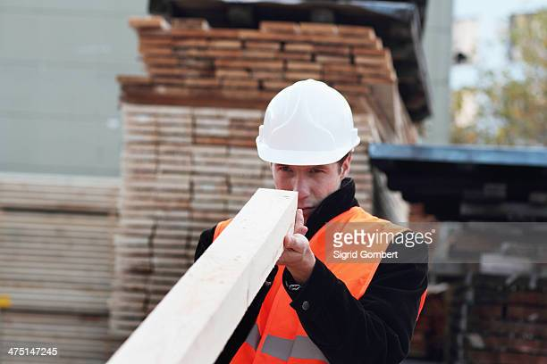 builder looking along plank of wood - sigrid gombert stock pictures, royalty-free photos & images