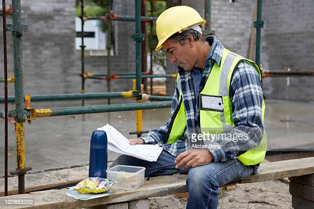 Builder looking at documents on constructon site