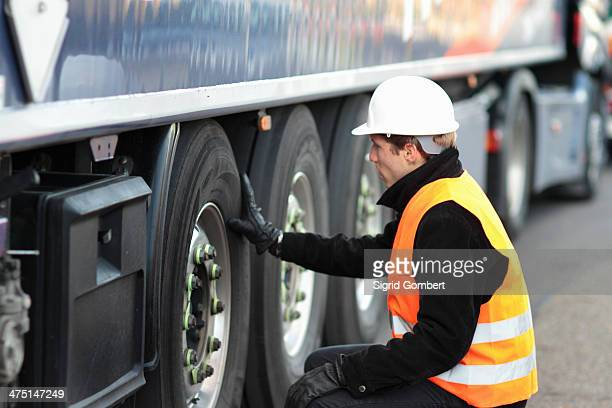 builder looking at wheel of truck - sigrid gombert stock pictures, royalty-free photos & images