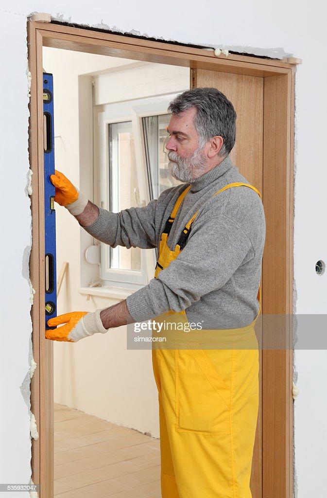 Builder measure verticality of door with level tool : Stock Photo