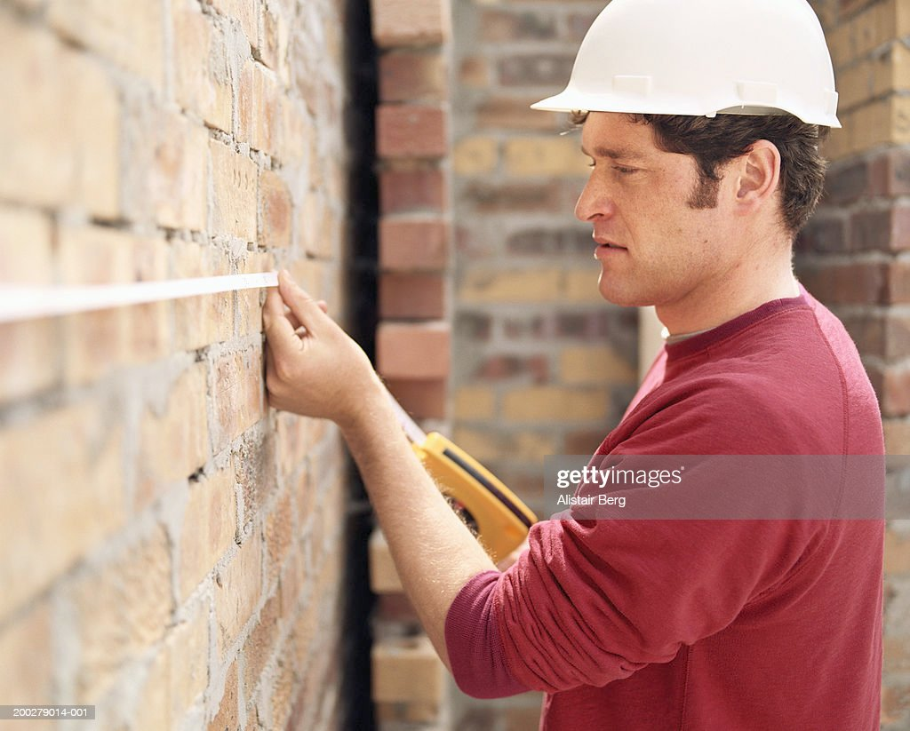 Builder Measuring Brick Wall Side View Stock Photo
