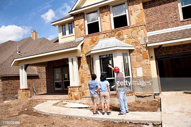 builder meeting with woman and daughter at new home construction - building contractor stock pictures, royalty-free photos & images
