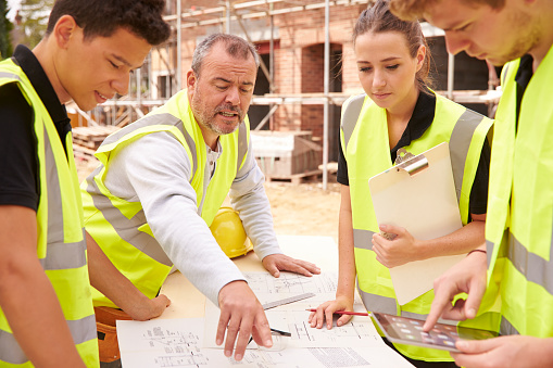 Builder On Building Site Discussing Work With Apprentice 483717764