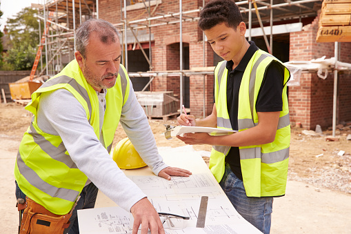 Builder On Building Site Discussing Work With Apprentice 483717780