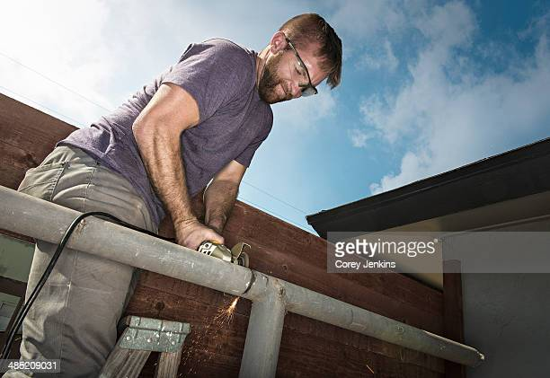 Builder on ladder sawing metal piping