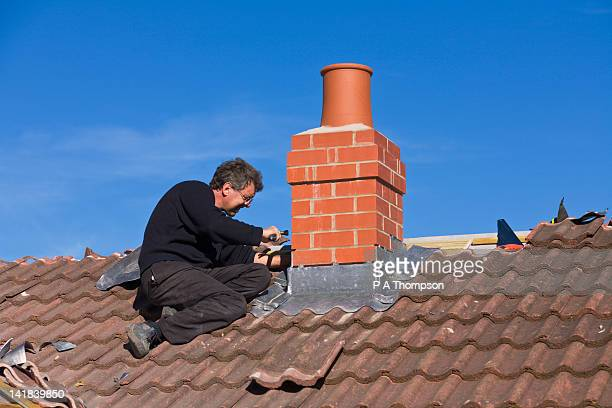 builder putting lead flashing around chimney stack - chimney stock pictures, royalty-free photos & images