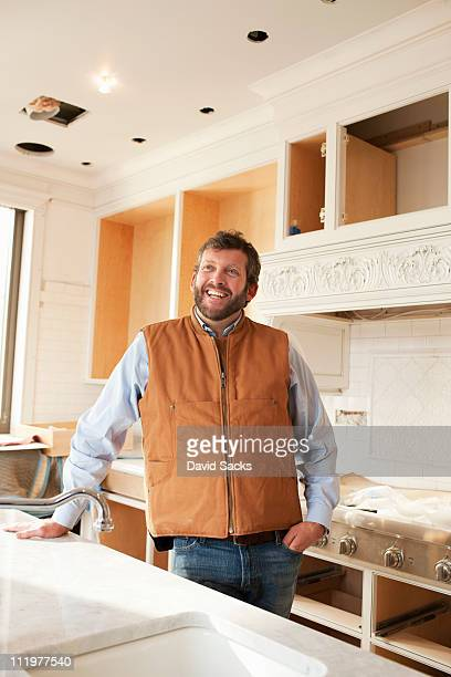 Builder smiling inside a kitchen under constructio