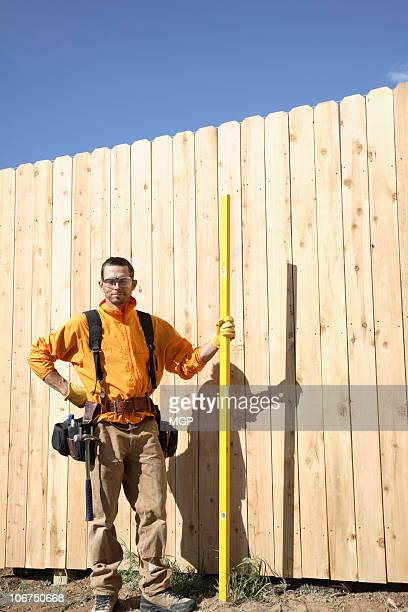 Builder stands by wooden fence