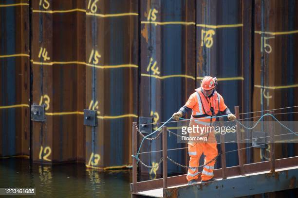 A builder stands on a gangway on the site of Wood Wharf a development by the Canary Wharf Group in the Canary Wharf business financial shopping...