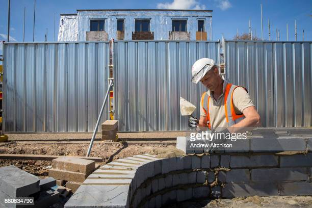 A builder uses a trowel and a spirit level to lay the first bricks with cement onto the foundations of a new house on a home building construction...