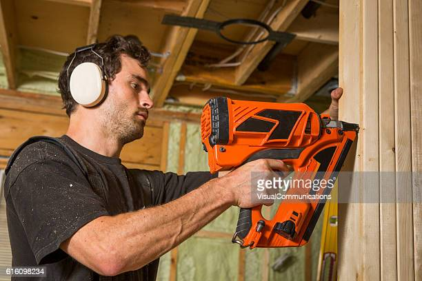 Builder using power tools inside the house.