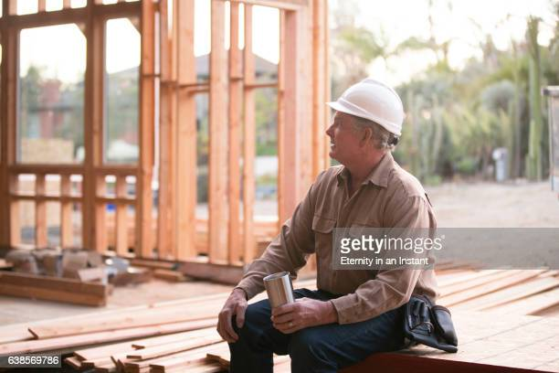 Builder walking with a plank of wood in an unfinished building