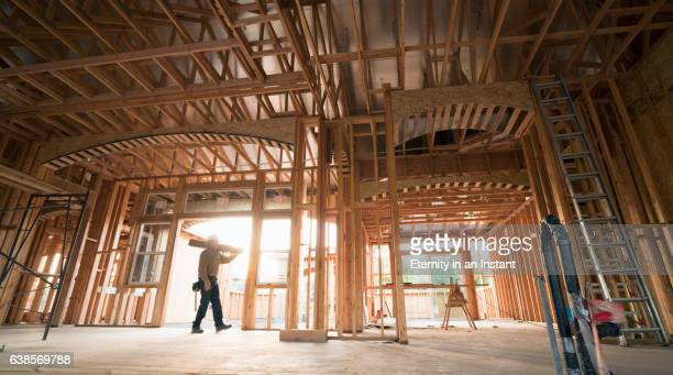 builder walking with a plank of wood in an unfinished building - intelaiatura foto e immagini stock