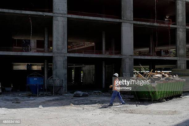 A builder walks past a building skip filled with timber as it sits on a social housing site under development by Spanish construction company Sacyr...