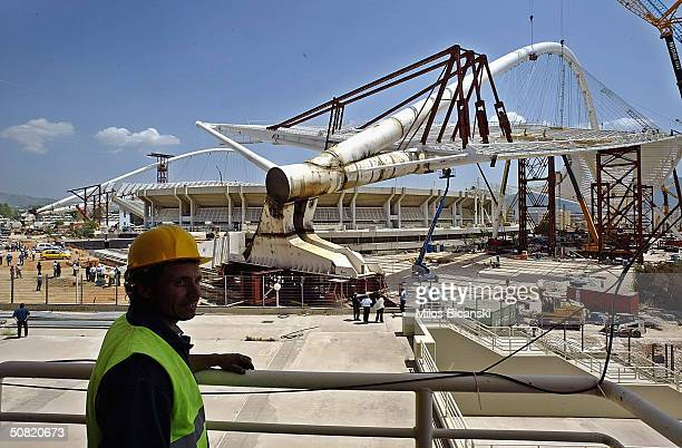 Builder watches the west side of the arch of the steel and glass roof of the Olympic Stadium moved in to place May 10, 2004 in Athens, Greece. The...